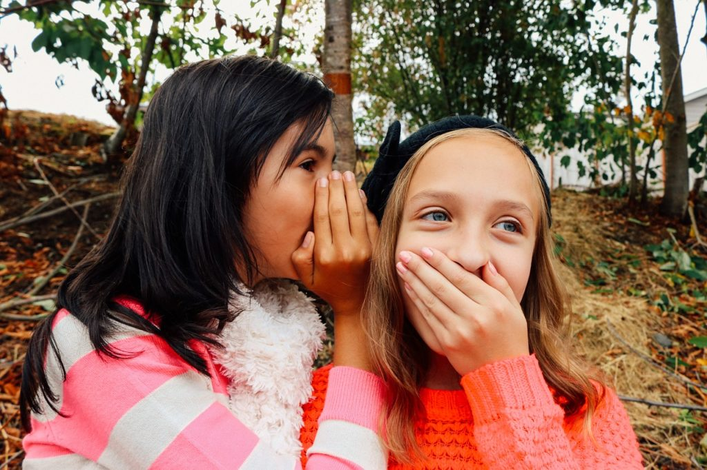 two girls playing listening games - areas to build child's language