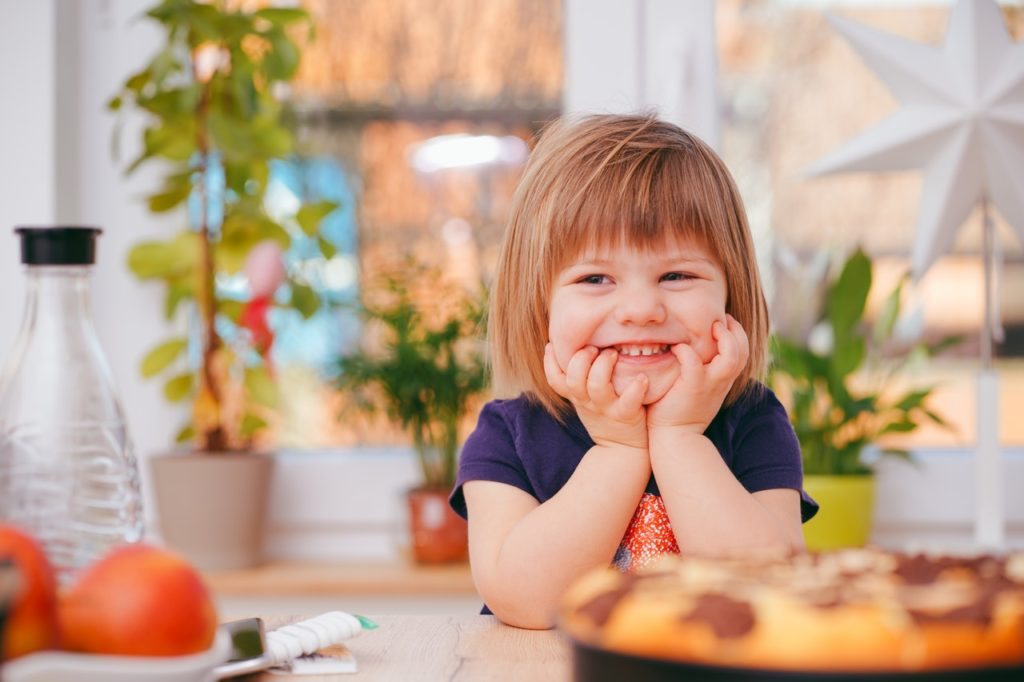 a girl smiling with a food in front of her - frugal living tips for moms in 2020