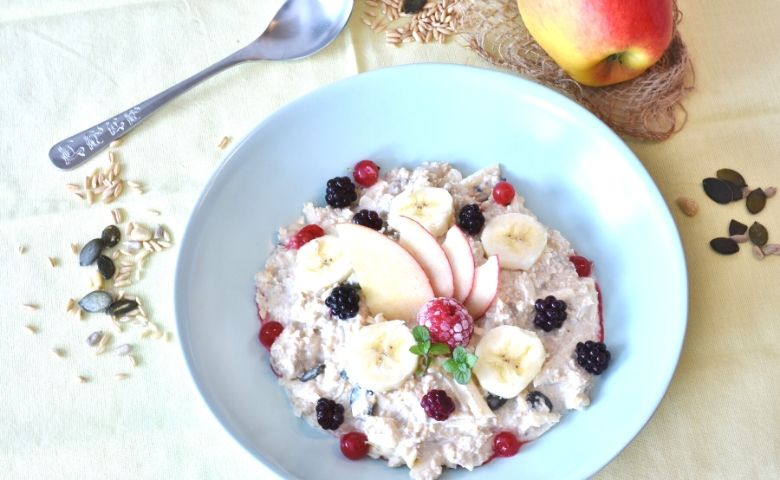 a bowl of oats, apples, berries and nuts